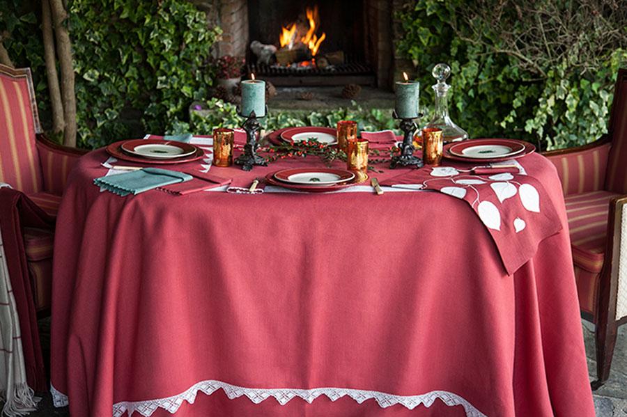 Mesa de mantel rojo con chimenea detrás